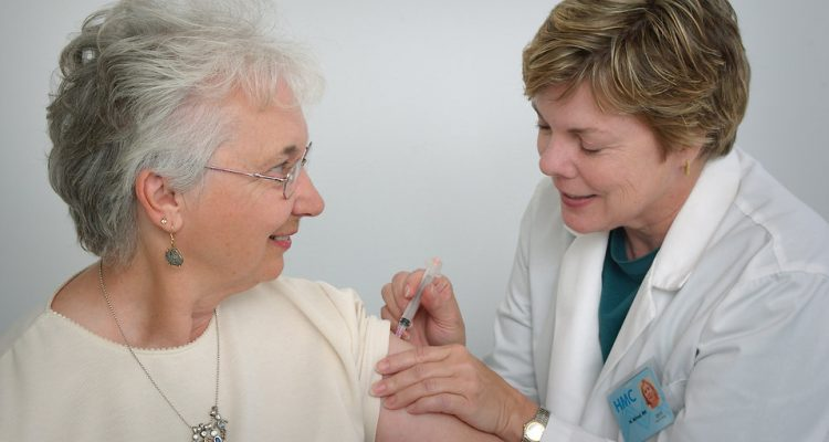 16730-a-nurse-giving-a-middle-aged-woman-a-vaccination-shot-pv